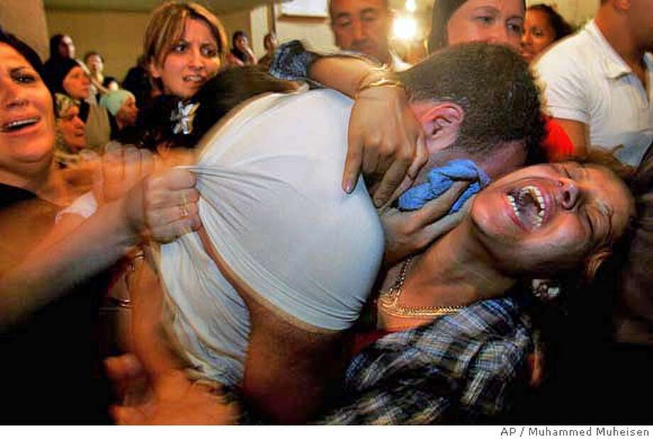 An Israeli Arab woman, relative of Marim Asadi, 26, grieves during a joint funeral for Asadi and her son Fathi, in the Arab town of Deir Al-Assad, in northern Israel, Thursday, Aug. 10, 2006. Asadi and her son Fathi, 5, were killed earlier Thursday in a Hezbollah rocket attack in the town. (AP Photo/Muhammed Muheisen) Photo: MUHAMMED MUHEISEN