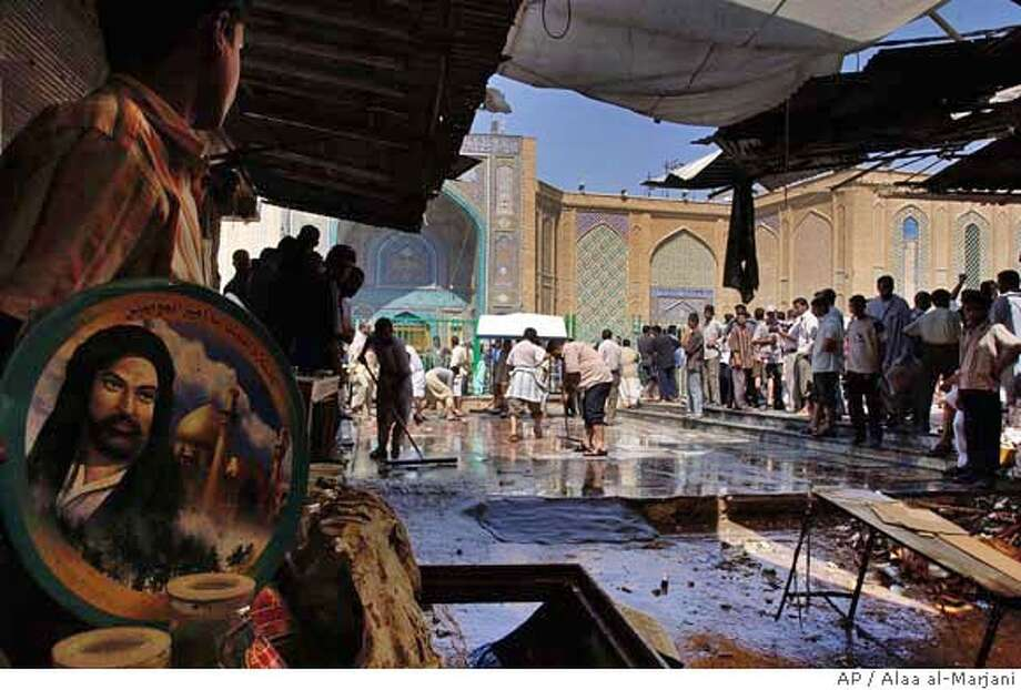 Locals clean the area in front of Imam Ali mosque, which contains the tomb of Prophet Muhammad's son-in-law, Ali, after a suicide bomber attack, in Najaf, 160 kilometers (100 miles) south of Baghdad, Iraq, Thursday Aug. 10, 2006. A suicide bomber detonated a belt of explosives on his body near a highly revered Shiite shrine in southern Iraq Thursday, killing at least 30 people and injuring 60, an official said. A picture of Imam Ali is seen at left. (AP Photo/Alaa al-Marjani) Photo: ALAA AL-MARJANI