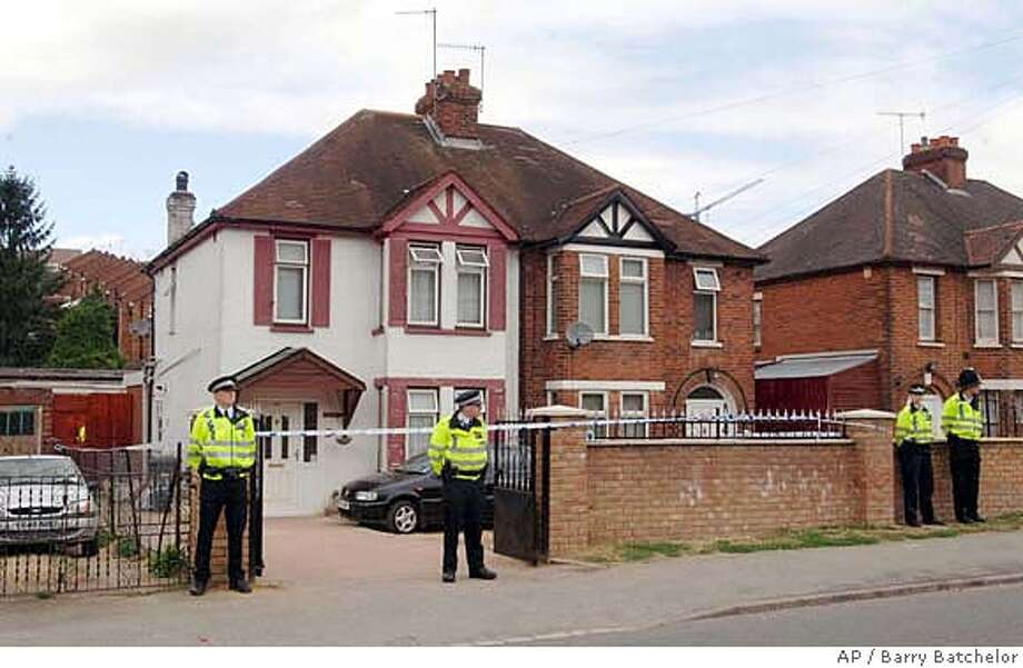 "Police officers stand outside a semi-detached house in High Wycombe, England, Thursday, Aug. 10, 2006, after a anti-terror raid. British authorities said Thursday they had thwarted a terrorist plot to simultaneously blow up several aircraft flying to the United States using explosives smuggled in hand luggage, averting what police described as ""mass murder on an unimaginable scale.""Police arrested 21 people, and were confident they had captured the main suspects in the alleged plot that U.S. authorities said bore the hallmarks of an al-Qaida plan. (AP Photo/Barry Batchelor/PA) ** UNITED KINGDOM OUT NO ARCHIVE ** UNITED KINGDOM OUT NO ARCHIVE - PHOTOGRAPH CAN NOT BE STORED OR USED FOR MORE THAN 14 DAYS AFTER THE DAY OF TRANSMISSION Photo: BARRY BATCHELOR"