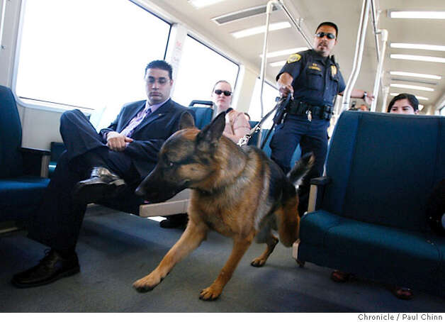 "BART police officer John Sandoval and his partner ""Tibo"" walk through an SFO-bound train that departed from the West Oakland station in Oakland, Calif. on Thursday, August 10, 2006 following the thwarted terrorist plot in Great Britain.  PAUL CHINN/The Chronicle  ** John Sandoval Photo: PAUL CHINN"