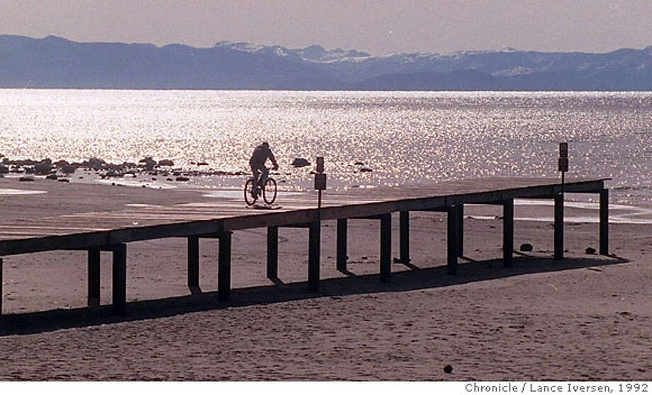 TAHOE/c/20NOV92/MN/LI. A cyclist makes his way to the end of the pier at Lake Tahoe's Kings Beach in this file photo dated Nov 20, 1992. by Lance Iversen, San Francisco Chronicle. Photo: LANCE IVERSEN