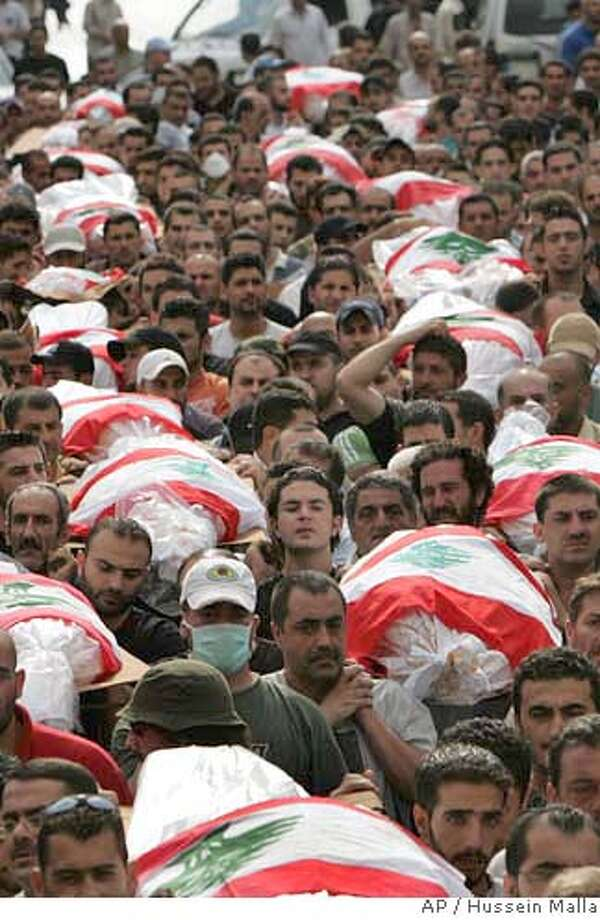 Mourners carry some of the flag-draped bodies of Lebanese citizens, killed when an Israeli airstrike hit an apartment building late Monday in the Beirut suburb of Chiah, during a mass funeral procession in the southern suburbs of Beirut, Lebanon, Wednesday Aug. 9, 2006. Lebanese security officials said the death toll in an Israeli airstrike in the region three days ago had risen to at least 41, with 61 wounded. (AP Photo/Hussein Malla) Photo: HUSSEIN MALLA