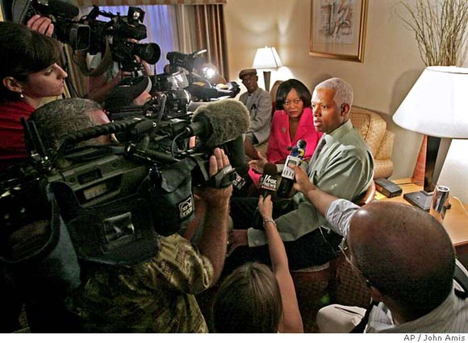 Democratic Congressional candidate Hank Johnson, seated at right, sits with his wife Mereda Davis Johnson while surrounded by journalists during a break from watching election returns in their hotel room in Decatur, Ga., Tuesday, Aug., 8, 2006. Johnson is in a primary run-off against U.S. Rep. Cynthia McKinney, D-Ga. (AP Photo/John Amis) Photo: JOHN AMIS