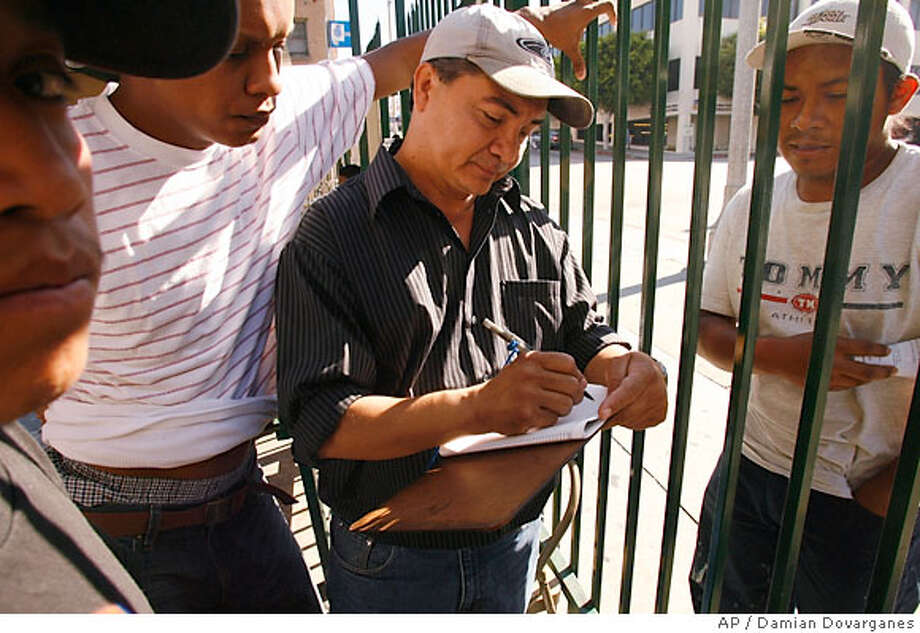 Day labor workers wait to sign in with site coordinator, Almicar Osegueda, center, at the Central American Resource Center, CARECEN, Wednesday Aug. 9, 2006 in Los Angeles. The nation's largest federation of unions agreed Wednesday to work with a network of day labor immigrants centers to improve wages and working conditions for the thousands of men who solicit work while standing on street corners across America.(AP Photo/Damian Dovarganes) Photo: DAMIAN DOVARGANES