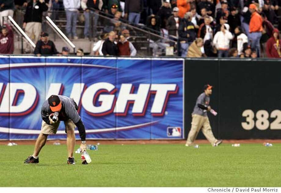 SAN FRANCISCO, CA - AUGUST 4: Workers remove trash from the field after Barry Bonds was thrown out of the game by home plate umpire Ron Kulpa in the 9th inning as the Giants play the Rockies on August 4, 2006 in San Francisco, California. (Photo by David Paul Morris/The Chronicle)  Ran on: 08-06-2006  Fans littered the AT&T Park field with trash Friday night. Unlike at the 'Stick, the wind didn't blow the litter out of the park. Photo: David Paul Morris