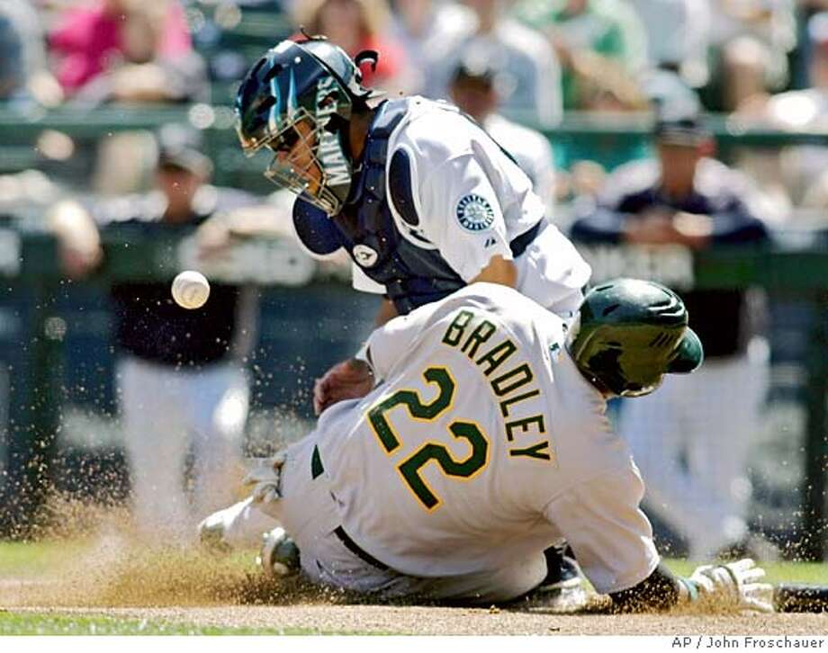 Oakland Athletics' Milton Bradley scores on a single hit by teammate Frank Thomas as the ball bounces away from Seattle Mariners catcher Rene Rivera during the first inning of their baseball game in Seattle Saturday, Aug. 5, 2006. (AP Photo/John Froschauer) Photo: JOHN FROSCHAUER