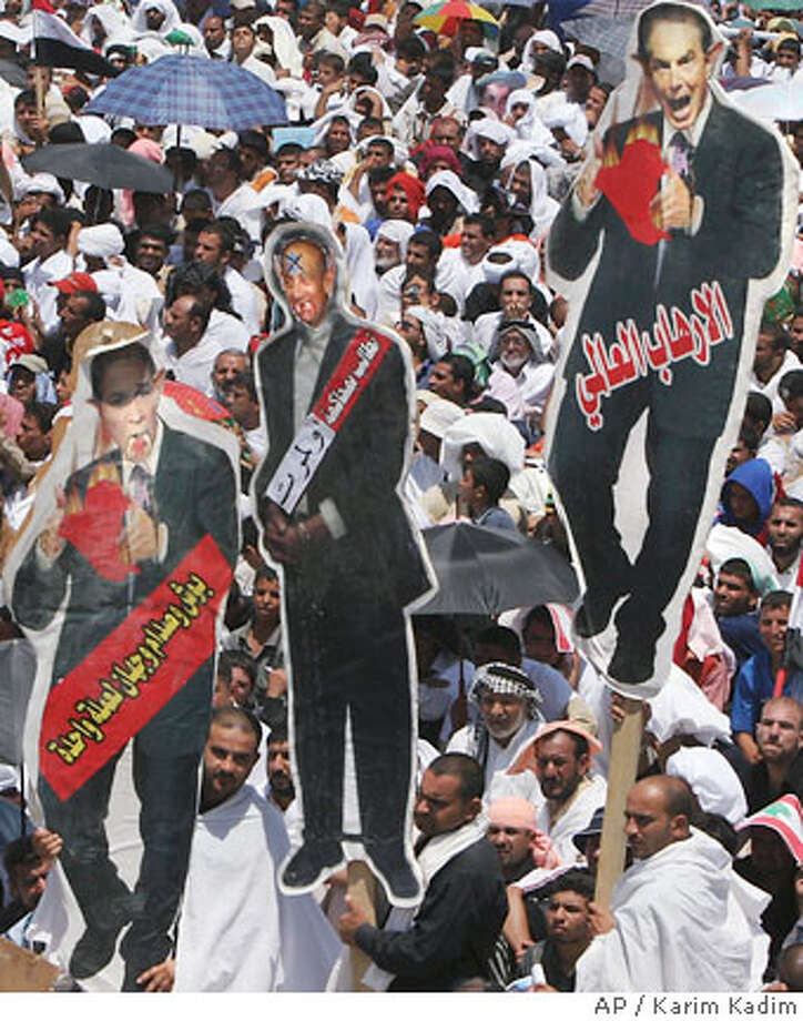 Carrying effigies of U.S. President George W. Bush, British Prime Minister Tony Blair and Israeli Prime Minister Ehud Olmert, Iraqi Shiites in the thousands gather in a mass demonstration against Israel's bombing of Lebanon, Friday, Aug. 4, 2006, in the Sadr City area of Baghdad, Iraq. Over 200,000 Shiites filled the streets of the Shiite dominated Sadr City slum to attend a rally in support of Lebanon after Friday prayers. (AP Photo/Karim Kadim) Photo: KARIM KADIM