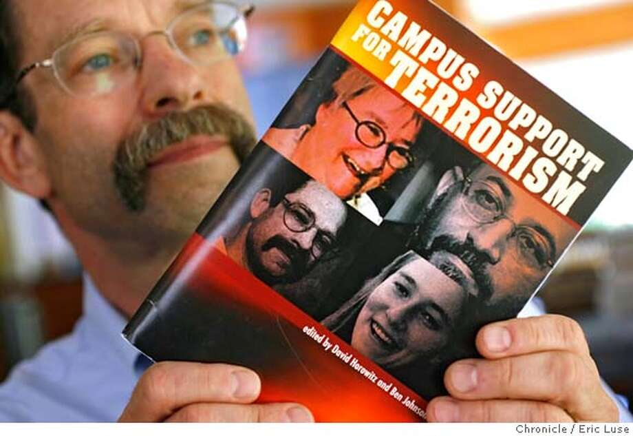 """stanford_beinin_0058_el.jpg  Photographed in his home in Palo Alto Stanford Middle East studies professor Joel Beinin holds the book his photo on the cover of a book put out by David Horowitz of the Center for Study of Popular Culture on a book called """"Campus Support for Terrorism""""  Clockwise on the book cover is Lynne Stewart, Sami al-Arian, Rachel Corrie and Joel Beinin. Photographed on June 8, 2006 in Palo Alto.  Eric Luse/The Chronicle MANDATORY CREDIT FOR PHOTOG / Photo: Eric Luse"""