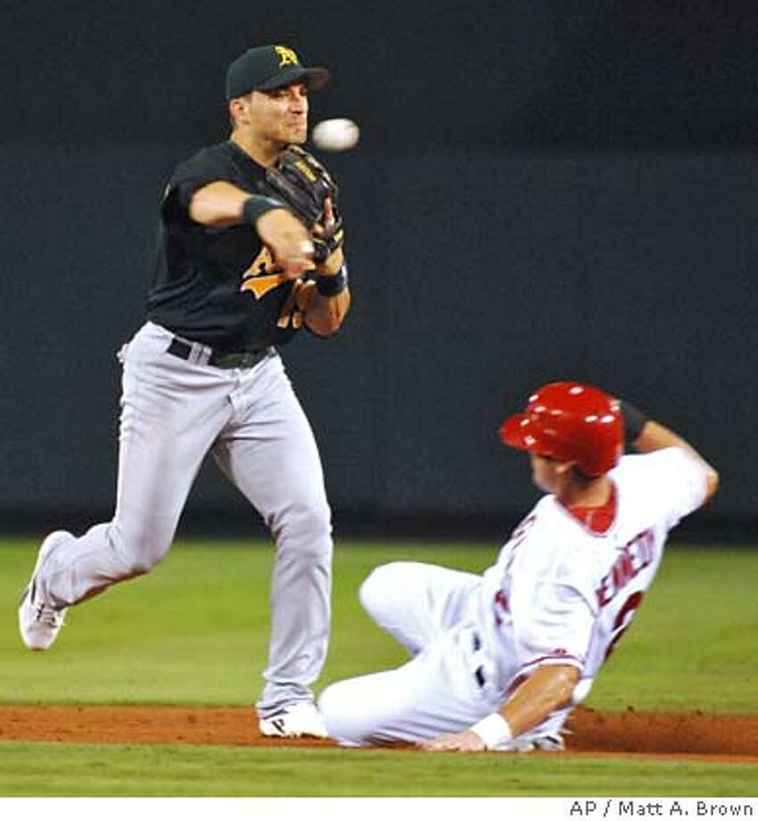 Oakland Athletics' Marco Scutaro turns the double play in the fifth inning as Los Angeles Angels' Adam Kennedy slides into second base during a baseball game Tuesday, Aug. 1, 2006, in Anaheim, Calif. (AP Photo/Matt A. Brown) Photo: MATT A. BROWN