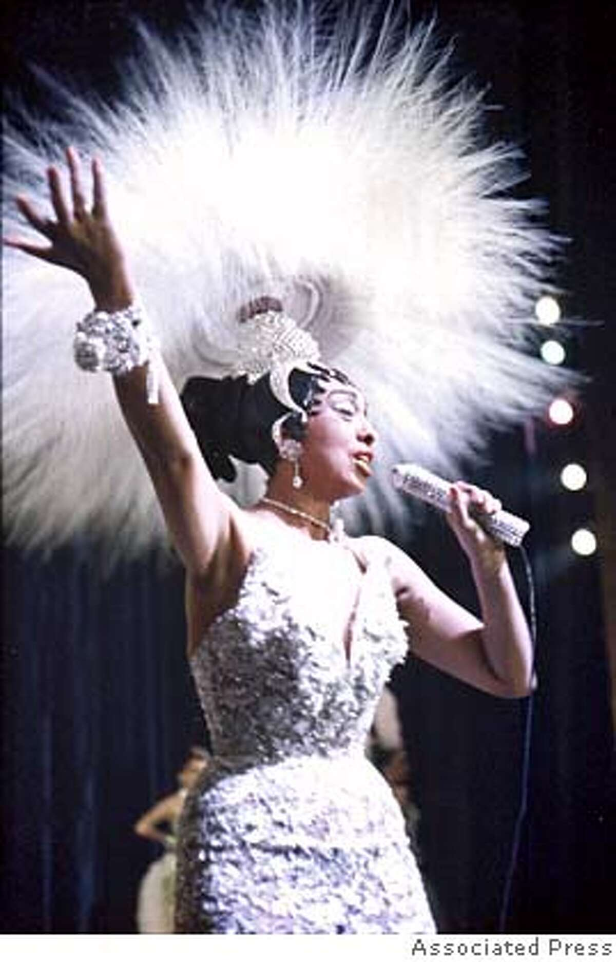 **FILE**Entertainer Josephine Baker holds a rhinestone-studded microphone as she performs during her show