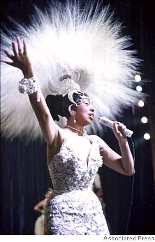 "**FILE**Entertainer Josephine Baker holds a rhinestone-studded microphone as she performs during her show ""Paris, mes Amours"" at the Olympia Music Hall in Paris, France, on May 27, 1957. Baker, aka ""Tumpie,"" her family nickname, was born in St. Louis 100 hundred years ago on June 3, 1906 and died April 12, 1975 after much acclaim.(AP Photo) A MAY 27 1957 FILE PHOTO Photo: Ap"