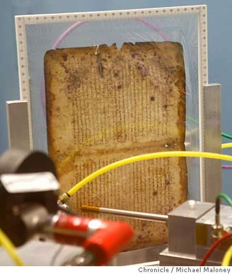 A page from the goatskin parchment manuscript is scanned by a special x-ray machine enclosed in a room at the Stanford Linear Accelerator Center.  After more than 1000 years in obscurity, the last unreadable pages of the works of ancient mathematician Archimedes are being deciphered, thanks to the x-ray vision at the Department of Energy�s Stanford Linear Accelerator Center (SLAC). A team of scientists are using a special x-ray imaging technique, called x-ray fluorescence (XRF) imaging, to finally unlock these scientific secrets, hidden from view on a goatskin parchment manuscript. Archimedes� work is considered to be the foundation of modern mathematics. The text of the Archimedes Palimpsest presented a challenge. In the 10th century, an anonymous scribe copied Archimedes� treatises in the original Greek onto the parchment. But three centuries later, the Archimedes text was scraped away and someone copied Greek Orthodox prayers onto the recycled pages. The result was the near obliteration of Archimedes� work, except for the faintest traces of ink still embedded in the parchment.  Photo by Michael Maloney / San Francisco Chronicle on 8/2/06 in Menlo Park,CA MANDATORY CREDIT FOR PHOTOG AND SF CHRONICLE/ -MAGS OUT Photo: Michael Maloney