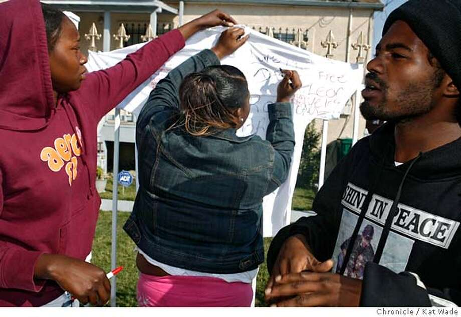 SHOTb_174_KW_.jpg (FAR RIGHT) Marice Sharp, 25, who claims to be the victim (Ron Ron's) older brother where's a sweat shirt with the photo of their cousin, 18, who was recently shot and killed in Oakland. (L to R) Ieisha Watson, 17 (who says she is the girlfriend of the victim's other brother) and Dbo Sexton, 23, a friend sign a memorial the three put up for Ron Ron on Wednesday Aug 02, 2006 at the location at 65th street and international Blvd. where a 17-year-old suspect who apparently opened fire on Oakland police in the neighborhood doing an undercover operation, was shot and killed by police last night.  Kat Wade/The Chronicle ** Dbo Sexton, 23, Marice Sharp, 25 and Ieisha Watson, 17, (Subjects) cq Mandatory Credit for San Francisco Chronicle and photographer, Kat Wade, Mags out Photo: Kat Wade