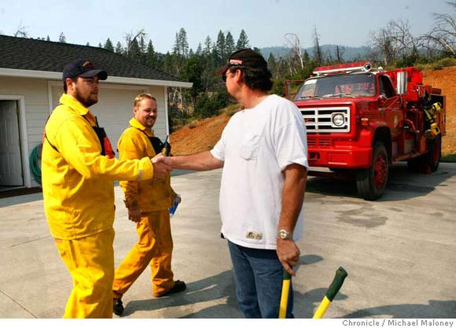 Weaverville homeowner Ron Fisher (right) thanks Shasta County firefighter Rob Leal (left) and his crew for protecting his home after the fire crew stood by throughout the weekend to protect his home. Fisher lost his home 4 years ago in a fire, rebuilding it on the same lot. Although he and his family were evacuated Saturday night, the flames never reached his house.  More than 1,500 firefighters battled a wildfire in the hills west of Weaverville in Trinity County. The Junction Fire, which started Saturday afternoon near Junction City, was burning east over Oregon Summit toward Weaverville's historic downtown. At one point, about 2,000 homes and 200 businesses were threatened however the fire was no longer threatening the town.  Photo by Michael Maloney / San Francisco Chronicle on 7/31/06 in Weaverville,CA MANDATORY CREDIT FOR PHOTOG AND SF CHRONICLE/ -MAGS OUT Photo: Michael Maloney