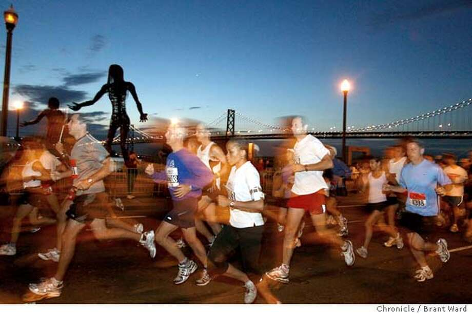 Runners began their trek at the Embarcadero in San Francisco where they first ran past views of the Bay Bridge. Elite runners started at 5:30am.  A record 15,000 runners were expected for the San Francisco Marathon Sunday July 30. The 26.2 mile citywide route took the runners through Golden Gate Park and the Golden Gate bridge under perfect conditions for running. {Brant Ward/The Chronicle} 7/29/06 Photo: Brant Ward