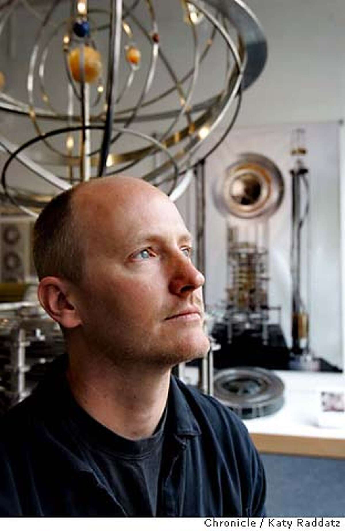 LONGNOW30_023_RAD.jpg SHOWN: Alexander Rose, the executive director of the Long Now Foundation. The model just behind Alexander is the prototype of the Orrery, which is the planetary display for the clock. The poster on the wall shows the first prototype of the clock. The Long Now Foundation is a group based in San Francisco that, among other things, wants to put a 10,000 year clock in the middle of the Nevada desert and store information and languages in forms that people hundreds of centuries from now will be able to benefit from. Photo taken on 7/14/06, in San Francisco, CA. (Katy Raddatz/The S.F.Chronicle) **Alexander Rose, Orrery Mandatory credit for photographer and the San Francisco Chronicle/ -Mags out
