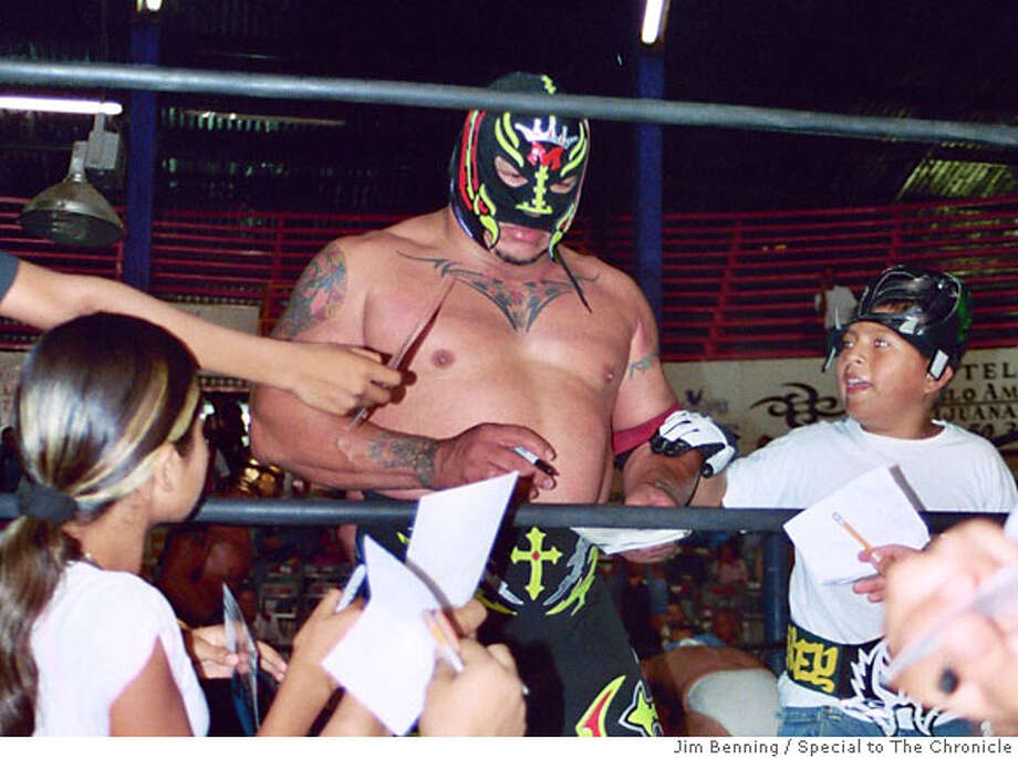 TRAVEL WRESTLING -- Lucha libre in Tijuana  Ran on: 07-30-2006  A wrestler signs autographs for young fans at a lucha libre ring in the Mexican border city of Tijuana. Photo: Jim Benning