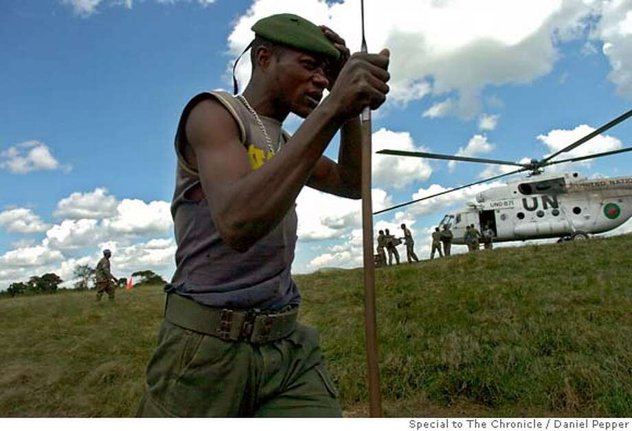 Tchei, DR Congo: A Congolese army soldier carrying a spear he took for a dead militia fighter walks past a UN helicopter as it unloads supplies for recently arrived South African peacekeepers.  (Photo credit: Daniel Pepper/Special to the Chronicle)  SFC Photo: Daniel Pepper Special To Chron.
