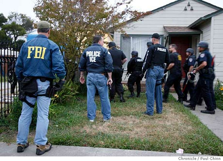 Law enforcement officials move in on a home on Monterey Street during a pre-dawn raid searching for members of the notorious MS13 street gang in Richmond, Calif. on Thursday, July 27, 2006. A joint operation between agents from Immigration and Customs Enforcement, the FBI and Richmond police officers took one man into custody and were searching for several others. PAUL CHINN/The Chronicle Photo: PAUL CHINN