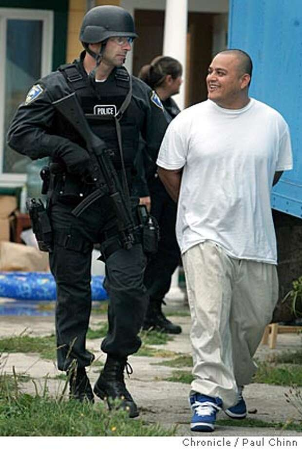 Jose Santos Bonilla is taken into custody by Richmond police officers after law enforcement officials conducted a pre-dawn raid on a home on Monterey Street searching for members of the notorious MS13 street gang in Richmond, Calif. on Thursday, July 27, 2006. A joint operation between agents from Immigration and Customs Enforcement, the FBI and Richmond police officers took one man into custody and were searching for several others. PAUL CHINN/The Chronicle  **Jose Santos Bonilla (Richmond Police Dept.) Photo: PAUL CHINN