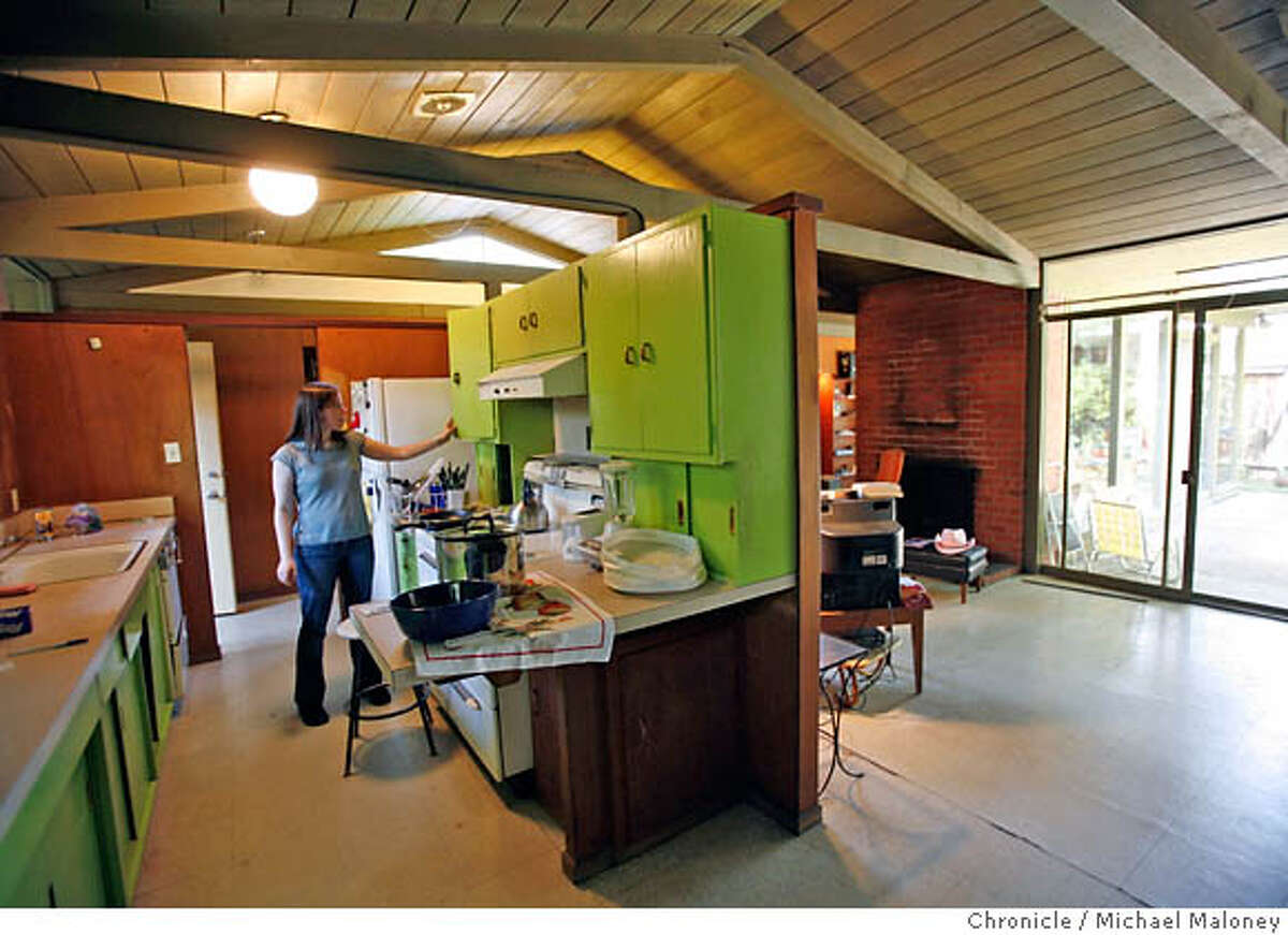 Kathleen Haley in the kitchen with it's lime green cabinets. Freelance writer Kathleen Haley has spent the past couple years living in her late grandmother's house with its retro orange lamp, chair and couch, and grandma's retro green kitchen. Although Eichler fans can't get enough of these Modernist houses, Haley isn't one of them, and her grandmother didn't do a lot of maintenance, so all the mid-century stuff is still in place and the million dollar home is falling apart. Photo by Michael Maloney / San Francisco Chronicle on 7/18/06 in Palo Alto,CA MANDATORY CREDIT FOR PHOTOG AND SF CHRONICLE/ -MAGS OUT