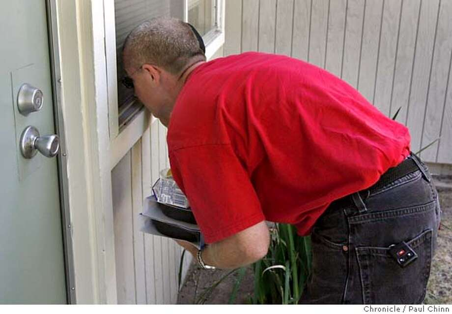Doug Lilly, who delivers food to the elderly for The Salvation Army, peeks through a window to make sure his client - who didn't answer the door - wasn't lying on the floor from heat stroke in Modesto, Calif. on Wednesday, July 26, 2006. The client wasn't at home. Lilly has yet to find anyone dead while on his rounds but dreads the day that it happens. Residents continued to cope with the blazing heat in this Central Valley city which experienced another day of triple-digit temperatures.  PAUL CHINN/The Chronicle  **Doug Lilly Photo: PAUL CHINN