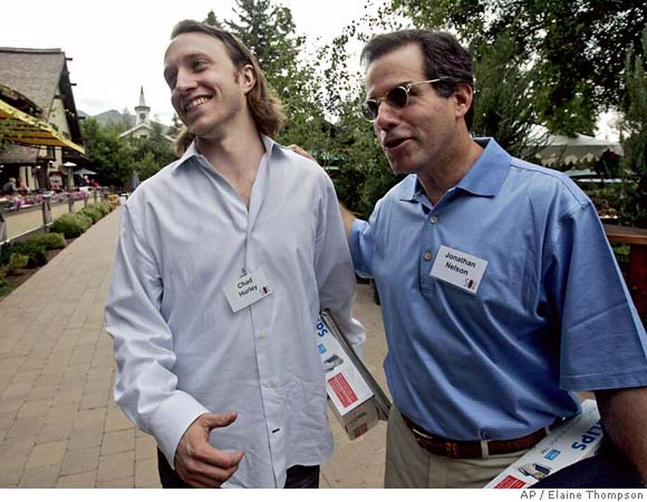 Chad Hurley, left, CEO of YouTube, Inc., gets attention from Jonathan Nelson, president and CEO of Providence Equity Partners Inc., after Hurley was interviewed Wednesday, July 12, 2006, at the annual Allen & Co. media conference in Sun Valley, Idaho. Just 17 months ago, Hurley was squirrelled away in a Silicon Valley garage running up a credit card debt as he and his business partner developed the quirkly Internet video site that became YouTube Inc. Now Hurley has become one of the star attractions at an elite media conference in Idaho, where the 29-year-old entrepreneur is seizing upon the attention to turn his San Mateo, Calif.-based startup into entertainment and advertising hub. (AP Photo/Elaine Thompson) Photo: ELAINE THOMPSON