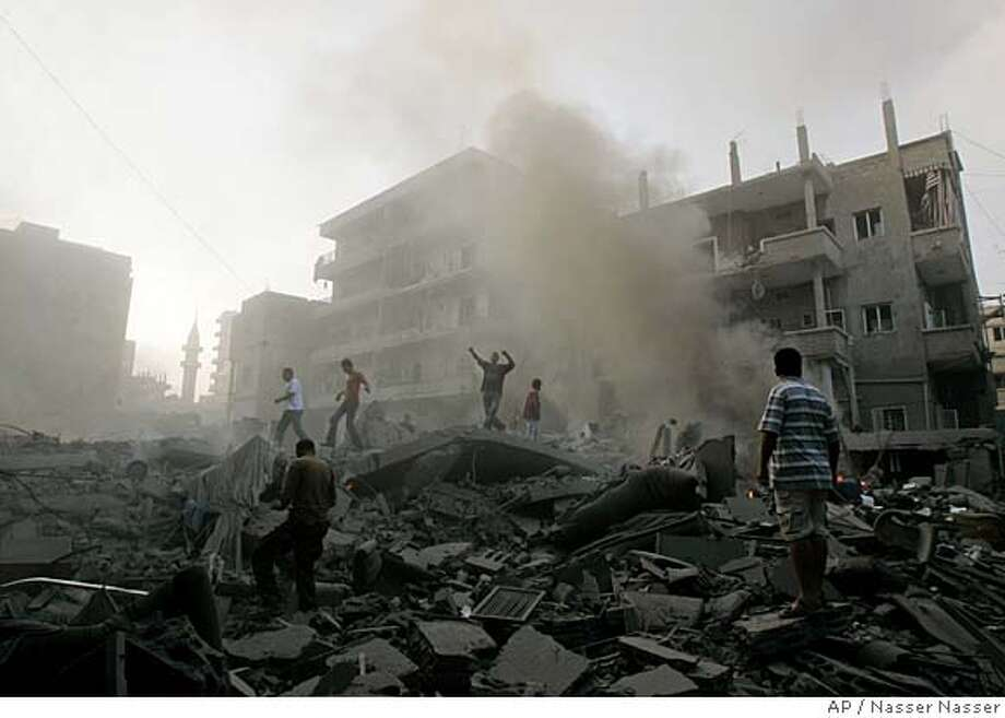 Lebanese men search for survivors, through the rubble at the site of a destroyed apartment building that was attacked by an Israeli warplane missiles in the southern coastal Lebanon city of Tyre, Wednesday, July 26, 2006. Hezbollah inflicted heavy casualties on Israeli troops as they battled for a key hilltop town in southern Lebanon for a fourth day Wednesday, with as many as 14 soldiers reported killed. Israel has faced fiercer resistance than expected as it advances across the border in its campaign against the Islamic militant group. (AP Photo/Nasser Nasser) Photo: NASSER NASSER