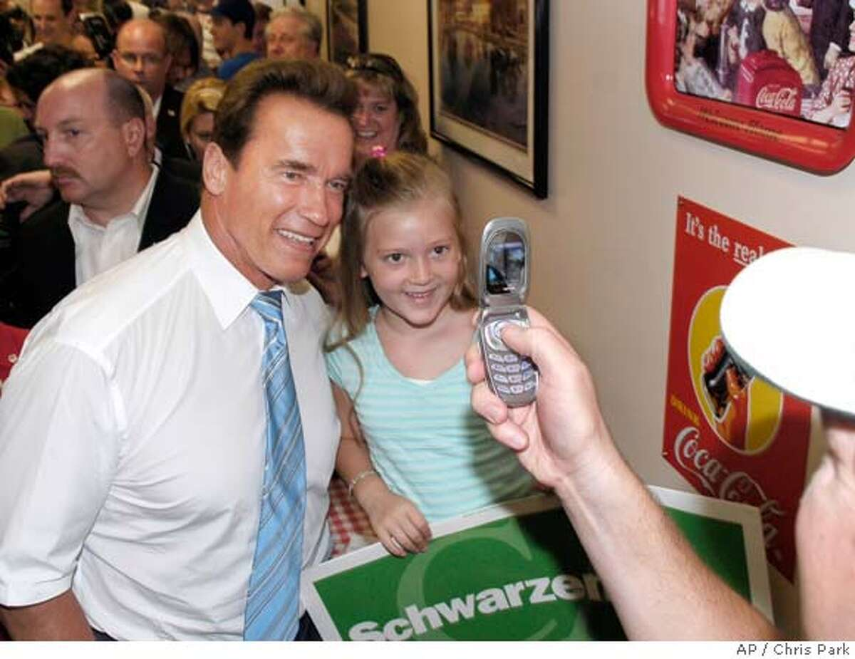 California Gov. Arnold Schwarzenegger poses for a picture during the second stop of a campaign bus tour through Southern California Tuesday, July 25, 2006, in Temecula, Calif. (AP Photo/Chris Park)