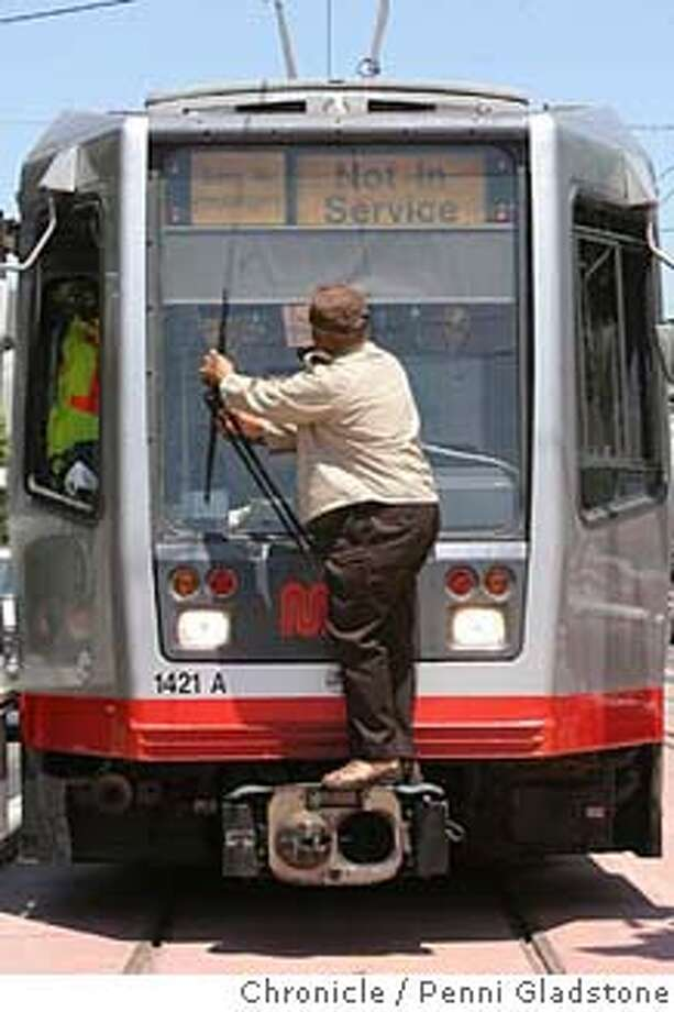 LIGHTRAIL26  On 3rd street in San Francisco, Melvin Clark a transit operator for Muni, checks the windshield wipers for any problems. The Municipal Railway began testing on its new Third Street light rail line SAN FRANCISCO CHRONICLE/PENNI GLASTONE  7/26/06 San Francisco Photo: Penni Gladstone