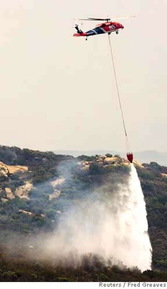 Fire helicopter drops water on wildfire in San Diego Photo: FRED GREAVES