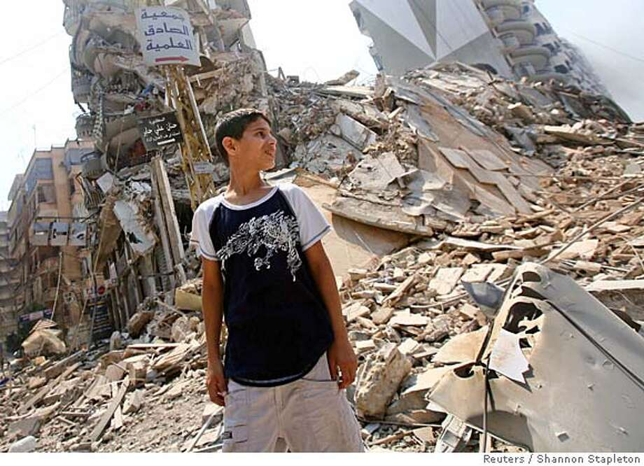 A Lebanese boy surveys the damage at the Hizbollah stronghold in the southern part of Beirut July 24, 2006. REUTERS/Shannon Stapleton (LEBANON) Photo: SHANNON STAPLETON