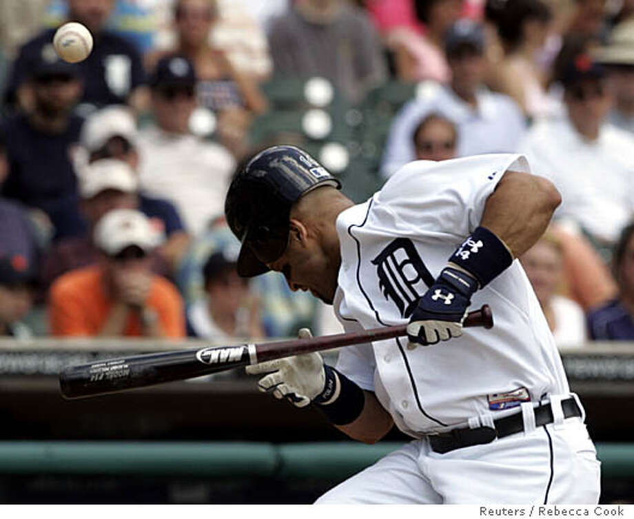 Detroit Tigers Placido Polanco reacts after being hit in the head by a pitch from Oakland Athletics starting pitcher Esteban Loaiza during the first inning of their American League baseball game in Detroit, Michigan July 23, 2006. REUTERS/Rebecca Cook (UNITED STATES) Photo: REBECCA COOK