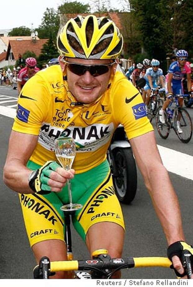 Phonak's team rider Floyd Landis of the U.S., wearing the leader's yellow jersey, holds a glass of champagne as he celebrates his overall leader position during the last stage of the 93rd Tour de France cycling race between Sceaux-Antony and the Champs-Elysees in Paris, July 23, 2006. REUTERS/Stefano Rellandini (FRANCE) Photo: STEFANO RELLANDINI