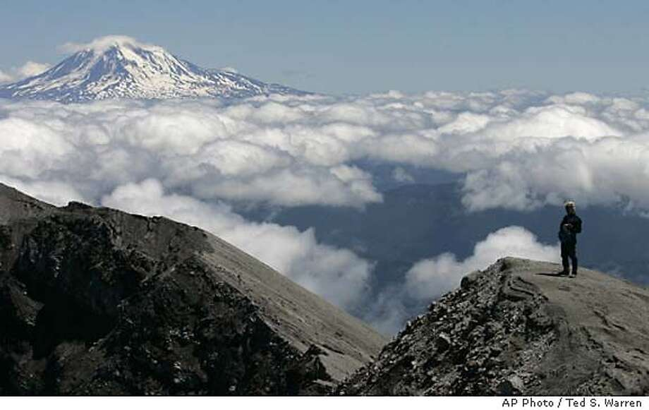 Top of the world: A news photographer stands on the rim of Mount St. Helens' crater before the mountain's public re-opening to climbers Friday. Mount Adams rises in the distance. Associated Press photo by Ted S. Warren