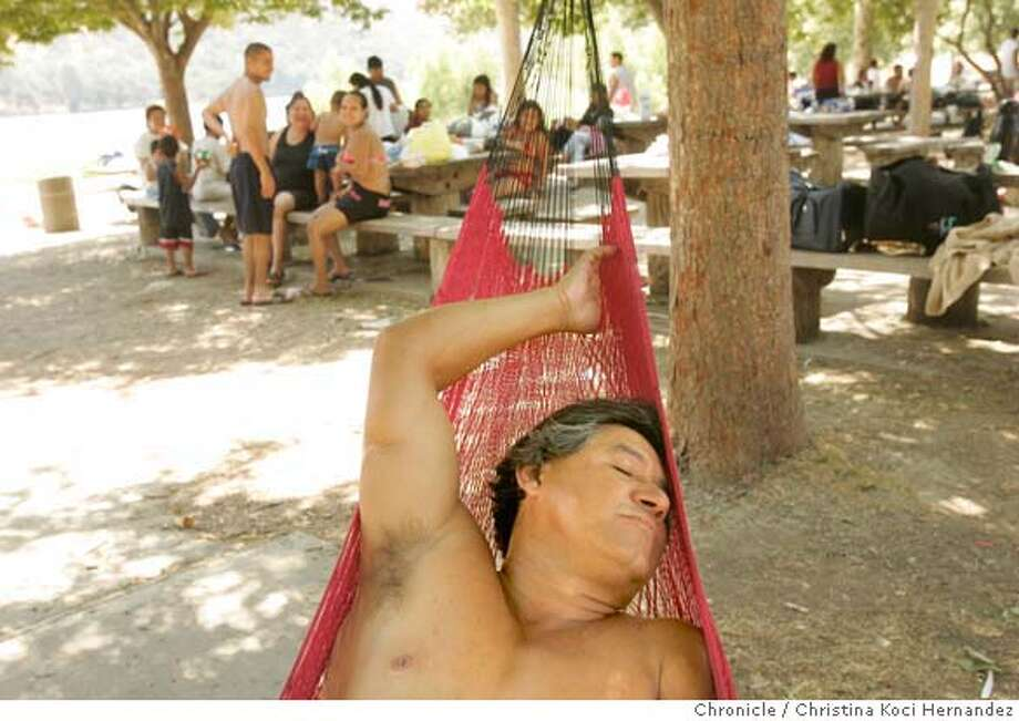 At Del Valle Regional Park, in Livermore, Alfonso Torres (cq) of San Jose, takes refuge from the heat in his hammock that he says he brings everywhere. The steady 111 degree weather drove people to find shade and to the beach at Del Valle Regional Park in Livermore..(CHRISTINA KOCI HERNANDEZ/THE CHRONICLE)  *Alfonso Torres Mandatory Credit For Photographer and San Francisco Chronicle/No-Sales-Mags Out Photo: Christina Koci Hernandez