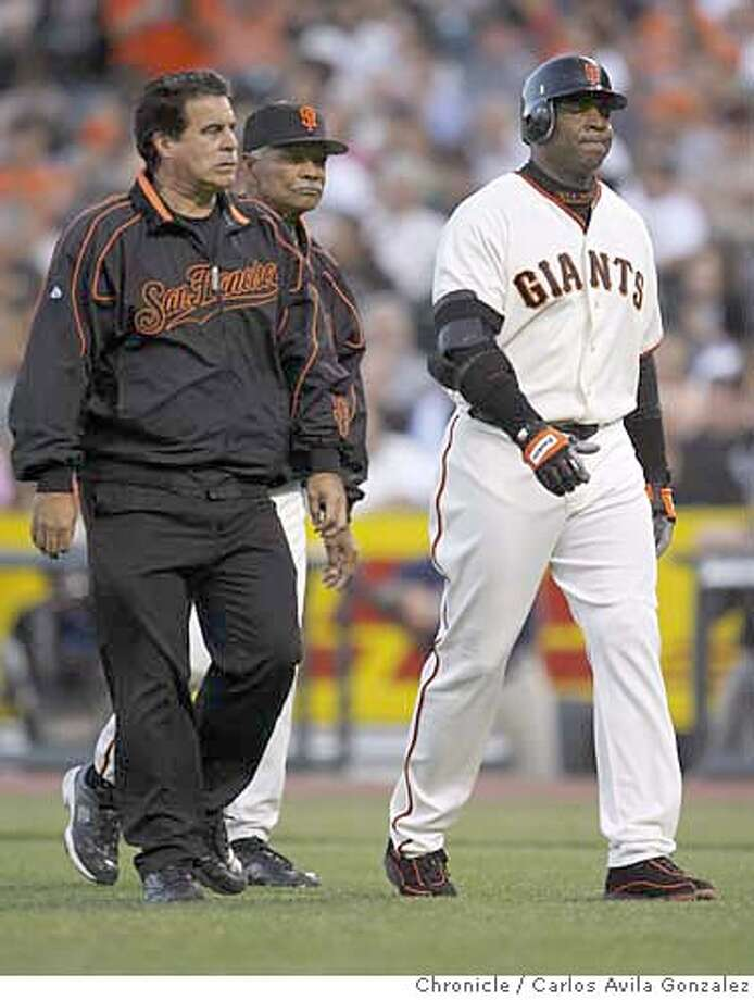 Barry Bonds makes a face as he walks off the field with trainer Stan Conte, left, and Manager Felipe Alou, rear, in the bottom of the third inning. Bonds complained of knee pain after sprinting to first base. He had been hit by a pitch in the knee in the bottom of the first inning. The San Francisco Giants play the San Diego Padres at AT&T Park in San Francisco, Ca., on Friday, July 21, 2006.  Photo by Carlos Avila Gonzalez/The San Francisco Chronicle  Photo taken on 7/21/06, in San Francisco, Ca, USA  **All names cq (Roster) Photo: Carlos Avila Gonzalez