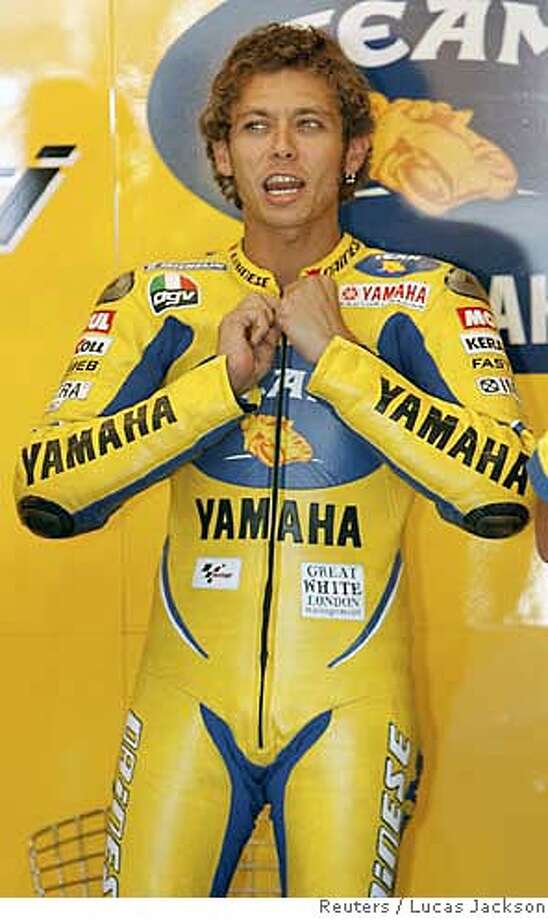 MotoGP rider Valentino Rossi of Italy dons his racing suit before a practice session for the upcoming U.S. Grand Prix at the Laguna Seca racetrack near Monterey, California July 21, 2006. REUTERS/Lucas Jackson (UNITED STATES) 0 Photo: LUCAS JACKSON