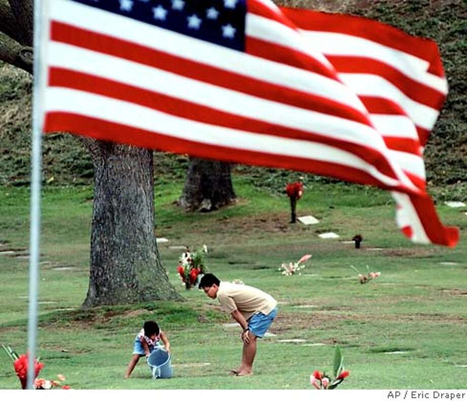 Mark Nakamura of Honolulu and his daughter Tiffany, 5, water the grass around the grave of his grandfather, a World War II veteran, at the Punchbowl National Cemetery of the Pacific, Thursday, Aug. 31,1995, in Honolulu. The cemetery will be the site of events commemorating the 50th anniversary of the end of World War II, V-J Day. President Clinton and foreign dignitaries from 27 countries will join up to 10,000 war veterans this weekend to mark the anniversary of Japan's surrender. (AP Photo/Eric Draper) Photo: ERIC DRAPER