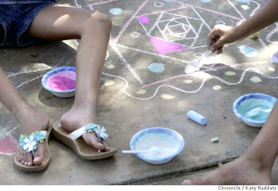 SUMMERCAMP00_016_RAD.jpg  SHOWN: Detail of children working on rangoli designs, which is traditional Indian art made with colored powders. The kids here sketch the designs with colored chalk on the driveway outside, then fill in the design with colored rice flour. The Chinmaya India Camp is one of many cultural camps available to kids this summer. This camp teaches kids kids many aspects of Indian culture, including tie-dying, rangoli (drawing with colored powders), Indian history and geography, etc. Photo taken on 7/18/06, in Palo Alto, CA.  (Katy Raddatz/The S.F.Chronicle)  **rangoli, Chinmaya Mandatory credit for photographer and the San Francisco Chronicle/ -Mags out Photo: Katy Raddatz