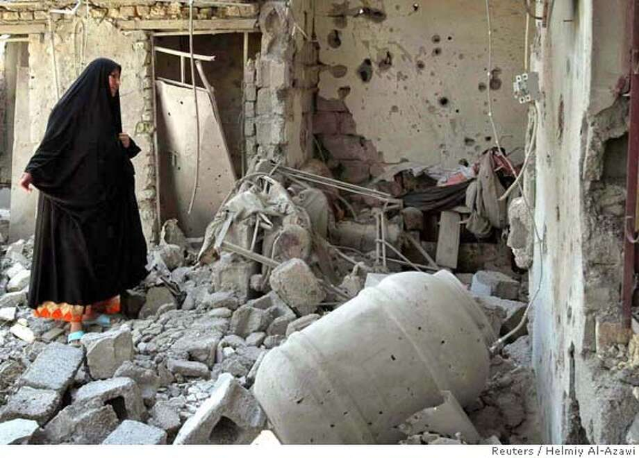 An Iraqi woman reacts as she arrives to a destroyed house where six members of the same family were killed in Baquba, 65 km (40 miles) northeast of Baghdad July 21, 2006. Six civilians from one Sunni family were killed when U.S. forces bombed their house in the northwestern side of Baquba on Friday, according to police and hospital sources. REUTERS/Helmiy Al-Azawi (IRAQ)  Ran on: 07-22-2006  An Iraqi woman reacts as she inspects a house that was destroyed in an Army Special Forces assault that killed five people and injured 25. A U.S. spokesman said two of the dead were linked to al Qaeda.  Ran on: 07-22-2006  An Iraqi woman reacts as she inspects a house that was destroyed in an Army Special Forces assault that killed five people and injured 25. A U.S. spokesman said two of the dead were linked to al Qaeda. Photo: HELMIY AL AZAWI
