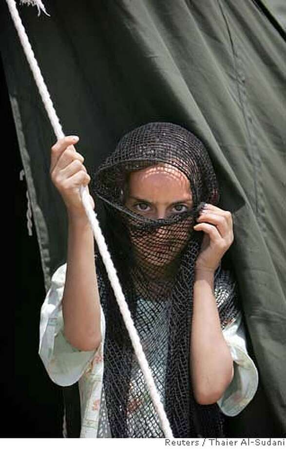 An internally-displaced Iraqi Sunni girl peers from behind her veil in a refugee camp in Baghdad July 20, 2006. Tens of thousands of Iraqis have fled their homes in fear of sectarian violence that has worsened since formation of a U.S.-backed national unity government two months ago, official data showed on Thursday. REUTERS/Thaier Al-Sudani (IRAQ) 0 Photo: THAIER AL-SUDANI