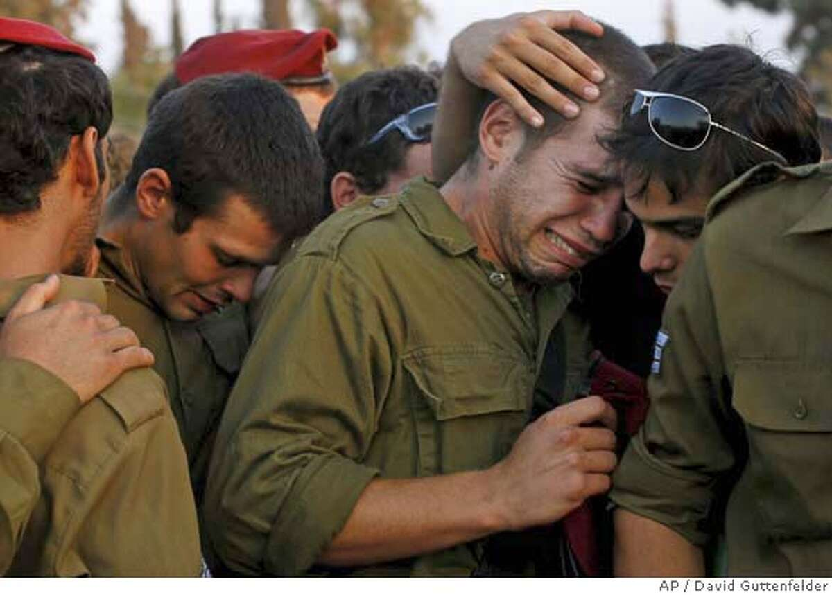 Israeli soldiers huddle together and grieve at the funeral of Yonatan Hadassi in Kibbutz Merhavya Thursday July 20, 2006. Hadassi was killed the day before in an exchange of fire with Hezbollah guerrillas on the Lebanon side of the border. (AP Photo/David Guttenfelder)