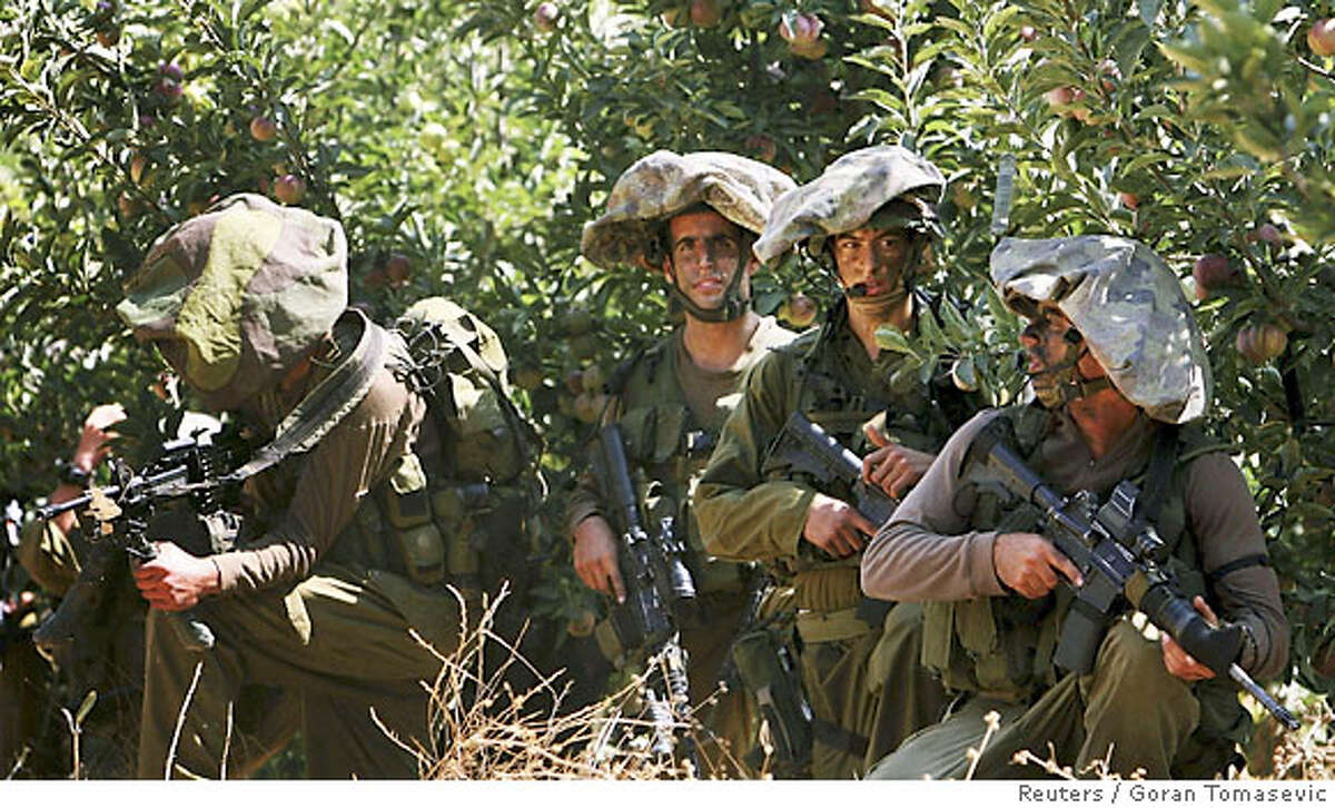 Israeli soldiers advance towards the Israel-Lebanon border