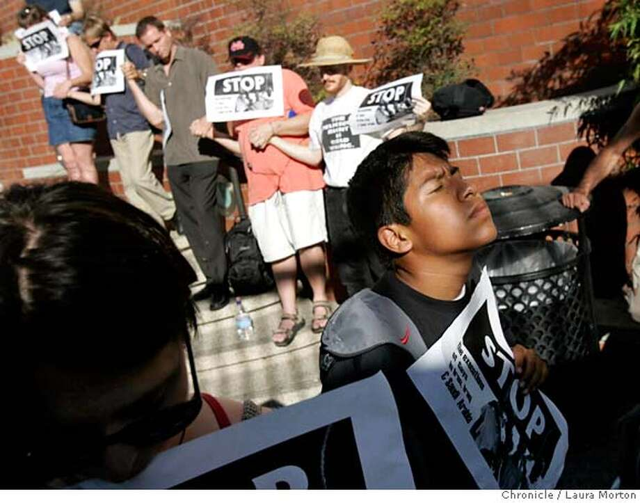 gayiran208802_lkm.jpg Erin Evans (left) and Heriberto Rodriguez (right) participate with others during a rally at Harvey Milk Plaza in remembrance of two Iranian teenagers who were publicly hanged one year ago. Reports from Iran claim that the teenagers were hanged because they were gay and in a sexual relationship with each other, while the Iranian government claims they were executed because they raped a young boy. Rallies and vigils for the same cause were held in over 20 cities around the world on Wednesday. Laura Morton/The Chronicle MANDATORY CREDIT FOR PHOTOGRAPHER AND SAN FRANCISCO CHRONICLE/ -MAGS OUT Photo: Laura Morton