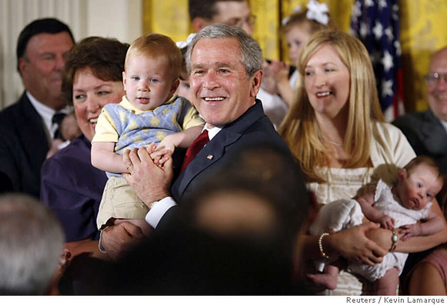 U.S. President George W. Bush holds Trey Jones, 1, of Cypress, Texas, after speaking out against federally-funded stem-cell research during an event at the White House in Washington July 19, 2006. Bush on Wednesday used his first veto to block legislation expanding embryonic stem cell research, putting him at odds with top scientists, most Americans and some in his own Republican Party. Jones, along with many other children onstage with the President, was conceived from frozen embryos. REUTERS/Kevin Lamarque (UNITED STATES) Photo: KEVIN LAMARQUE