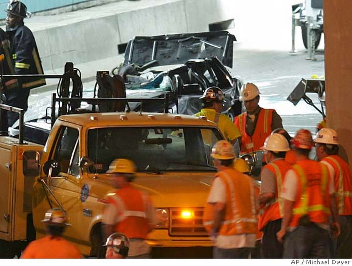 Emergency personnel work at the scene of a ceiling collapse in the Interstate 90 eastbound tunnel through Boston that crushed a car, rear, killing a woman passenger, Tuesday, July 11, 2006. (AP Photo/Michael Dwyer)