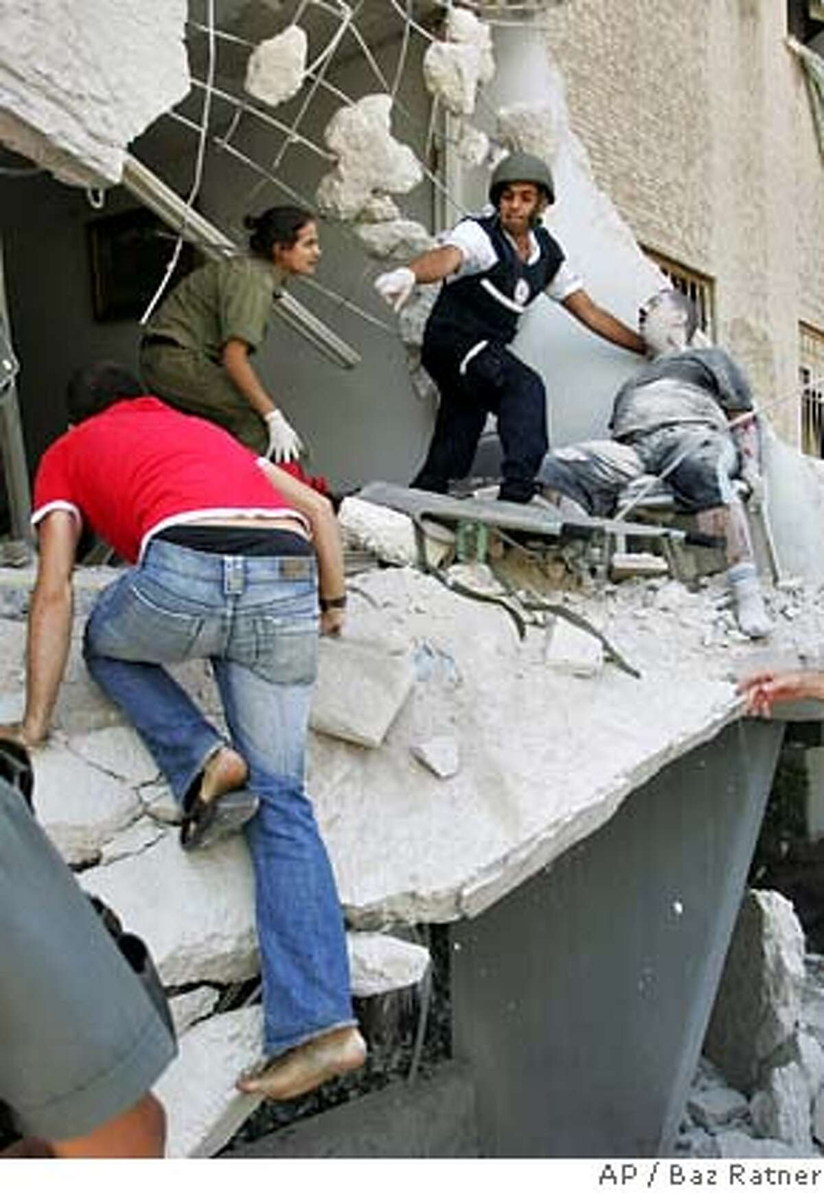 ** RETRANSMISSION FOR ALTERNATE CROP ** Rescue workers evacuate a seriously wounded man from a building directly hit by a rocket fired from Lebanon in the northern Israeli city of Haifa, Monday July 17, 2006. Hezbollah guerrillas fired several volleys of rockets at the city of Haifa on Monday, destroying a three-story building and wounding at least three people, Israeli medics said. (AP Photo/Baz Ratner)