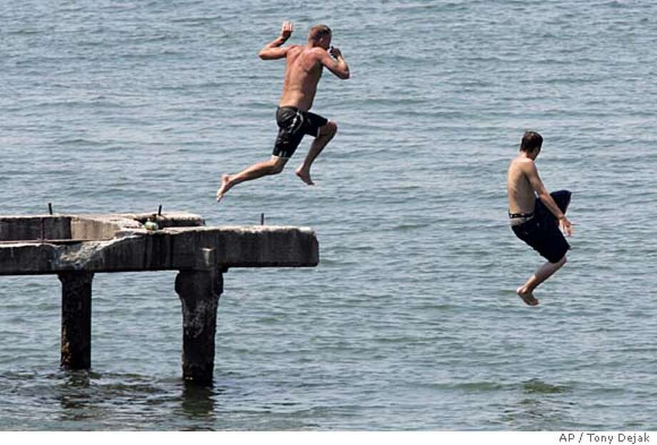 Two boys jump off a pier, Monday, July 17, 2006, at Edgewater Park, in Cleveland. It took half a summer to get here, but Ohio is into its first heat wave of the year. Temperatures of 90-95 were expected across the nation and throughout Ohio on Monday with the potential to break records of 91 in Mansfield and 93 in Youngstown, said Mike Dutter, meteorologist with the National Weather Service in Cleveland. (AP Photo/Tony Dejak) Photo: TONY DEJAK