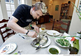 CHEFSFAVES_058_RAD.JPG SHOWN: Chris Cosentino is the chef, here at home, about to dish up the Whole Roasted Black Bass he has made for dinner, to serve with a lovely arugula and fennel salad. His wife Tatiana Graf and 16-mo-old son Easton Graf will enjoy the bounty. Photo taken on 5/16/06, in SAN FRANCISCO, CA.  By Katy Raddatz/San Francisco Chronicle  **Easton Graf, Tatiana Graf, Chris Cosentino